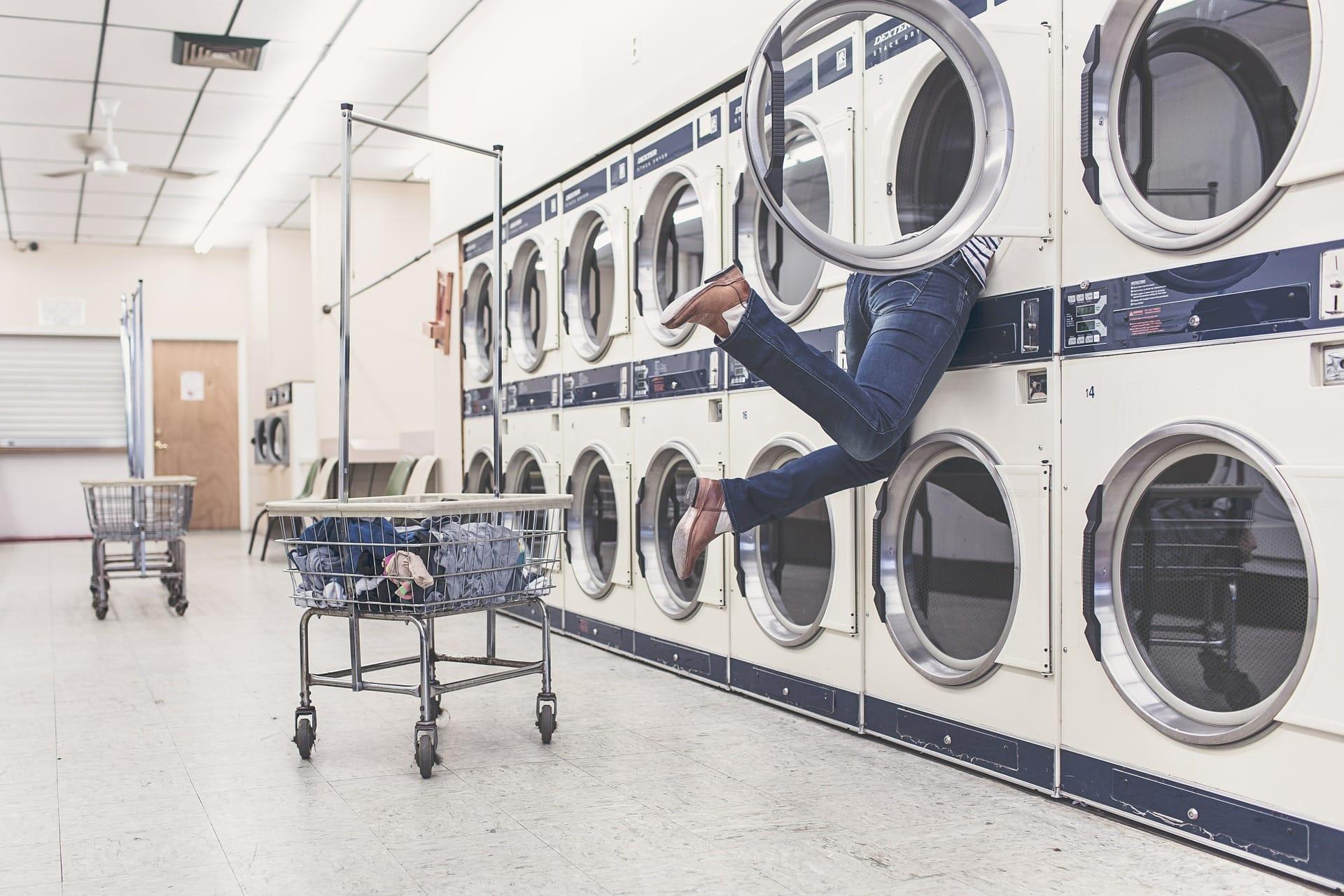 Mensch steckt Kopf in eine Waschmaschine um nach der Lösung für ein Problem zu suchen. Daneben steht ein Einkaufswagen mit Wäsche.