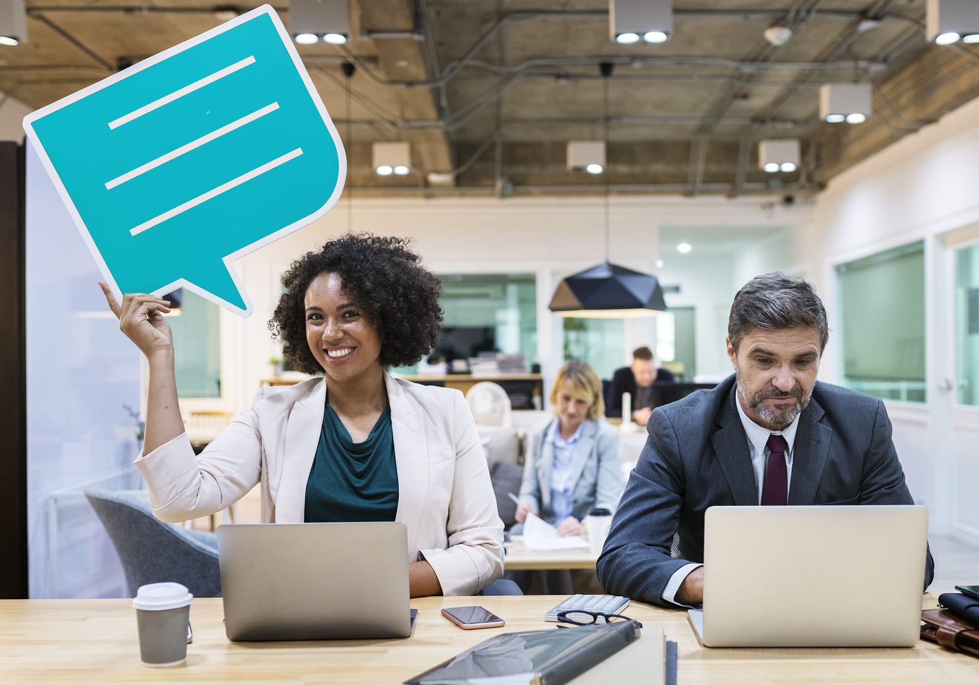 Arbeitende Menschen im Büro mit Laptop und Sprechblase zum mitteilen von Erfahrungen.