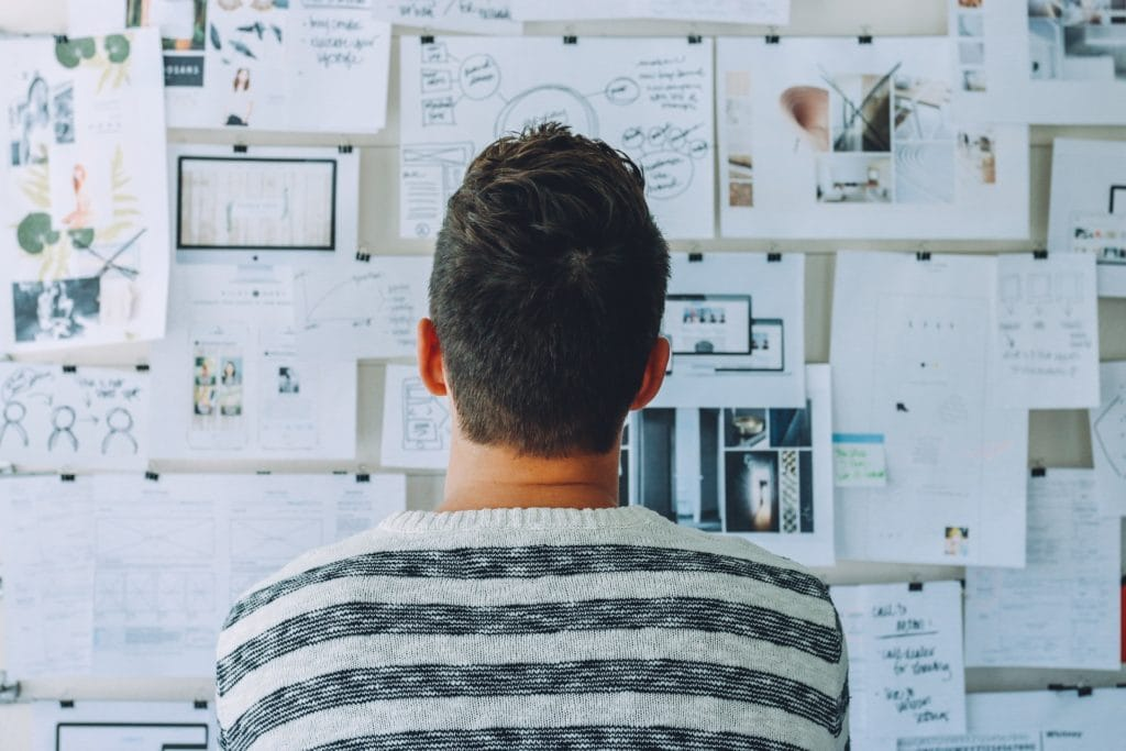 Konzeption durchdenken und Strategie entwickeln wie dieser Mann mit Whiteboard und Zetteln an der Wand